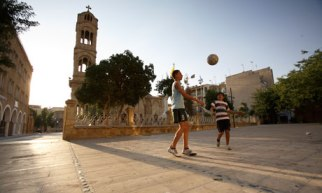 Children play football outside Phaneromeni Church near the 'green line' that separates Cyprus